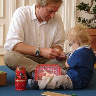 Ankerland: Dr. Andreas Krüger mit einem Kind in einem Therapieraum von Ankerland e.V.