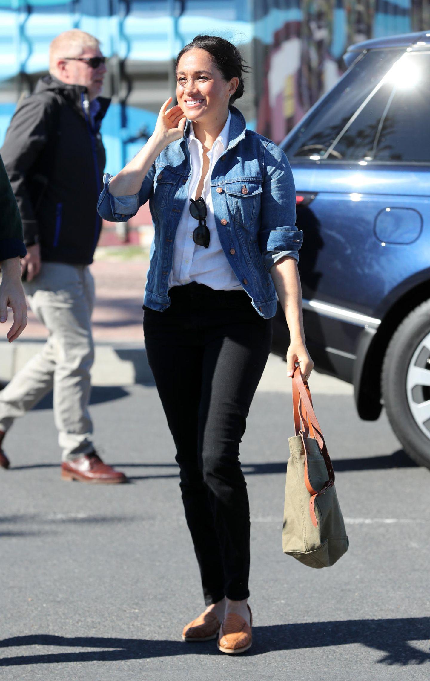 """Wow, was für ein ungewöhnlicher Look. Tag zwei ihrer Afrikatour startet leger. Auf dem Weg zur NGO """"Waves for Change"""" am Monwabisi Strand setzte Meghanauf eine sportliche Jeans, eine einfache weiße Bluse, eine bleue Jeansjacke und ein flache Espadrilles. dazu kombinierte sie einen großen Shopper und eine Sonnenbrille, die sie sich lässig in den Ausschnitt steckte.      auf Kleidund hohe Schuhe setzt Meghan diesmal auf eine sportliche Jeans, eine einfache weiße Bluse, eine bleue Jeansjacke und paar flache Espadrilles."""