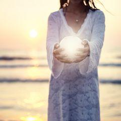 Mondzeichen: Eine Frau steht am Meer und hält einen kleinen Mond in den Händen
