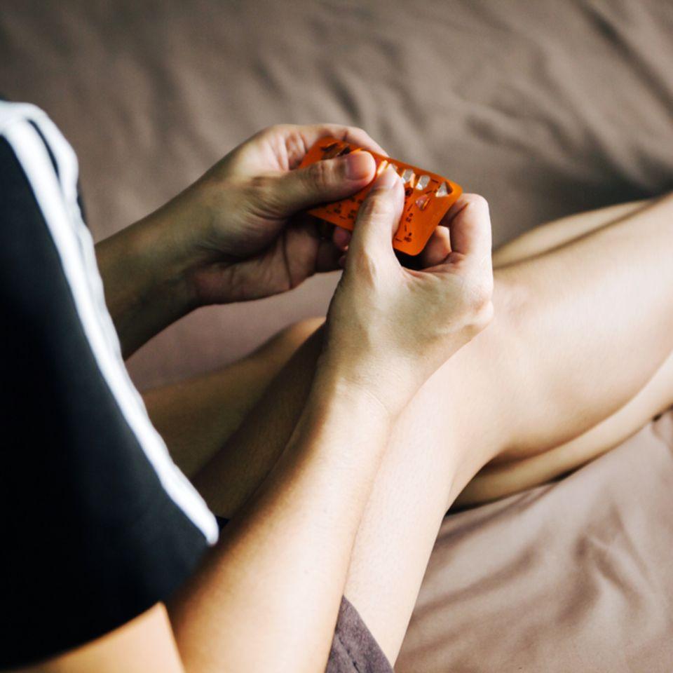 Frau mit Anti-Baby-Pille in  der Hand