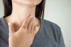 Kehlkopfentzündung: Frau fasst sich an den hals