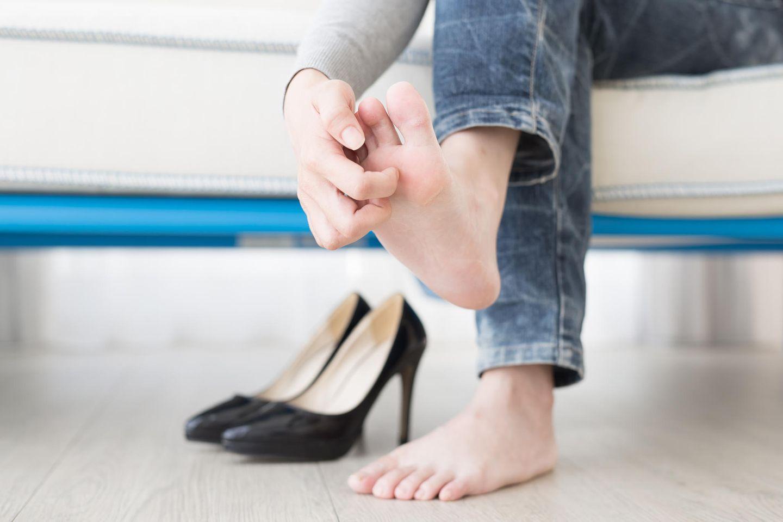 Hausmittel gegen Fußpilz: Frau kratzt sich an Fußsohle