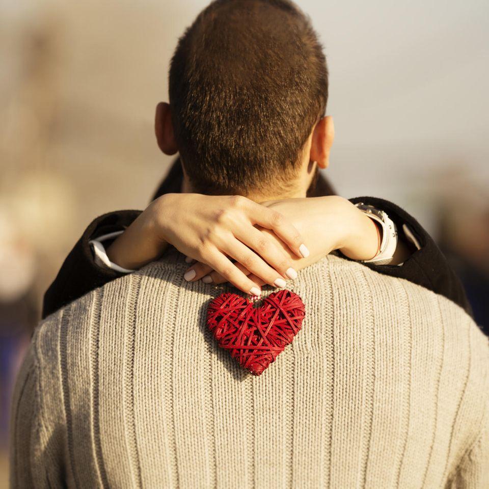 Horoskop: Eine Frau umarmt einen Mann mit einem Herz in der Hand