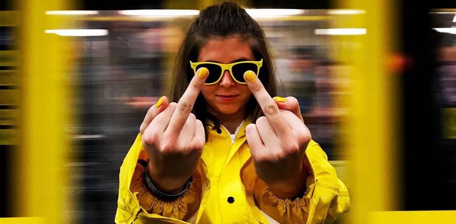 Frau in Gelb zeigt Stinkefinger