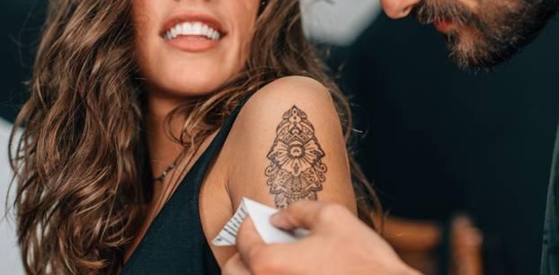 Tattoo-Ideen für Zwillinge: Frau mit Tattoo auf dem Oberarm