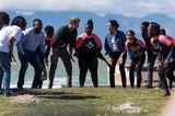 Herzogin Meghan + Prinz Harry in Afrika: Meghan Markle und Prinz Harry stehen im Kreis