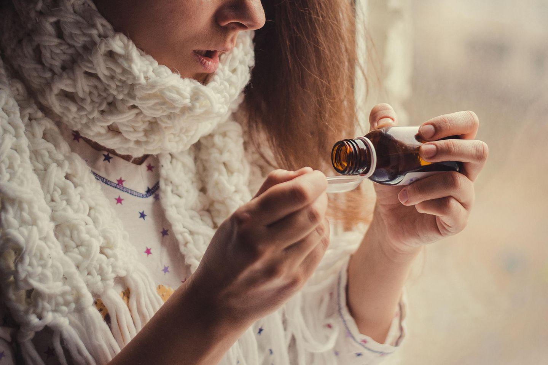 Akute Bronchitis: Frau nimmt Hustensaft ein