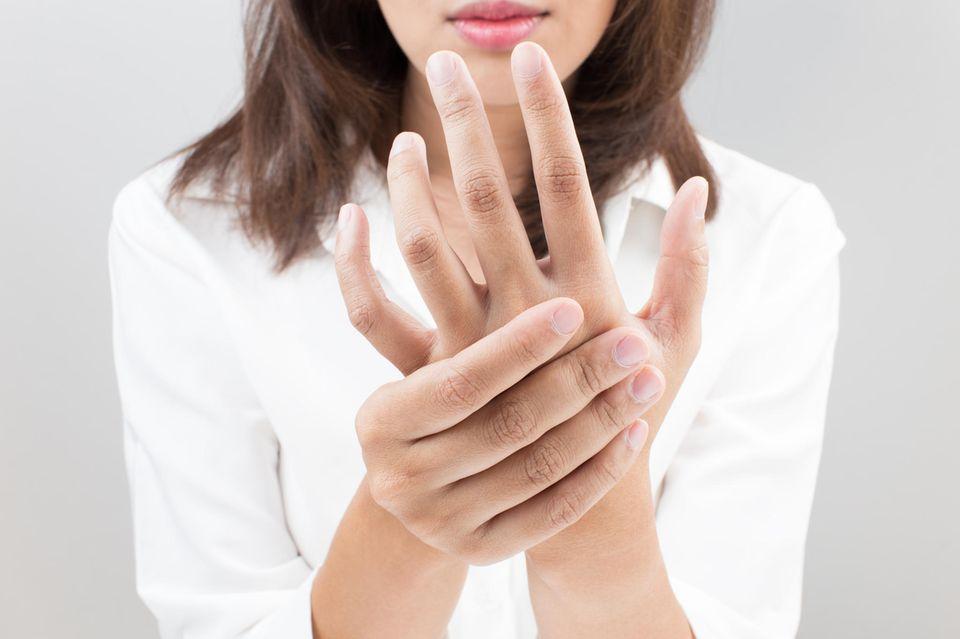 Sehnenreizung: Anzeichen, Ursachen und Behandlung: Frau hält ihre linke Hand