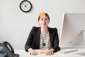 Denkfallen im Job: Frau mit Post it auf Stirn