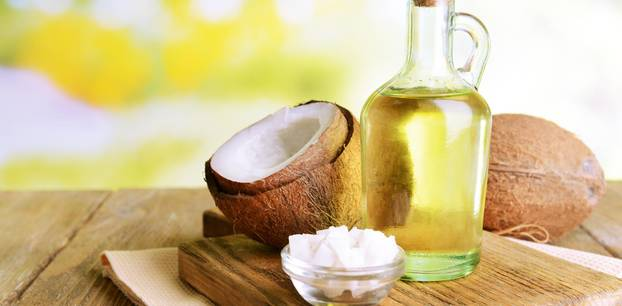 Mit Kokosöl abnehmen: Kokosöl und Kokosnuss auf Holztisch