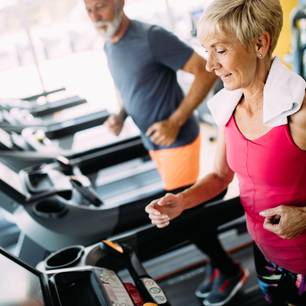 Wieviel Sport in welchem Alter?: Ältere Dame und älterer Herr trainieren auf Laufband.