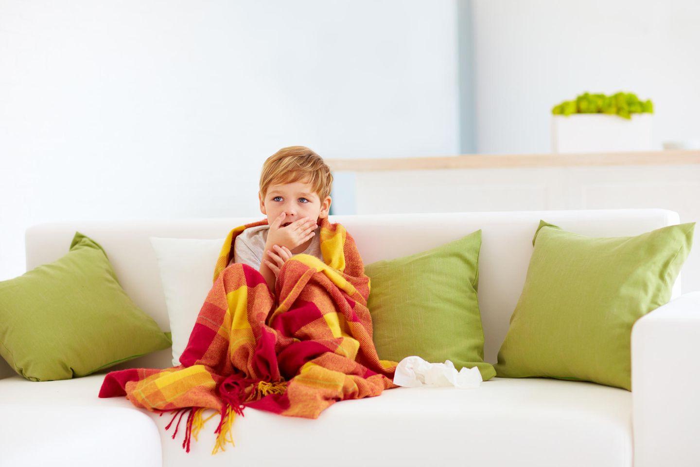 Spastische Bronchitis: Krankes Kind auf dem Sofa