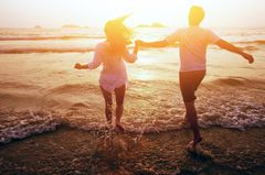 Ein Pärchen läuft im Sonnenuntergang Richtung Meer