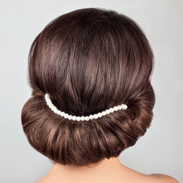Frisuren selber machen: Frau mit eingedrehten Haaren und Perlenband