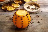 Bastelideen Weihnachten: Kerzenständer aus Orange mit Nelken