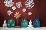 Bastelideen Weihnachten: Schneeflocken aus Papier und Holzhäuser