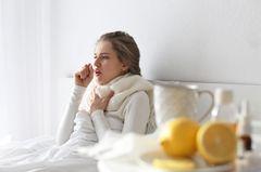 Ist Bronchitis ansteckend? Kranke Frau im Bett