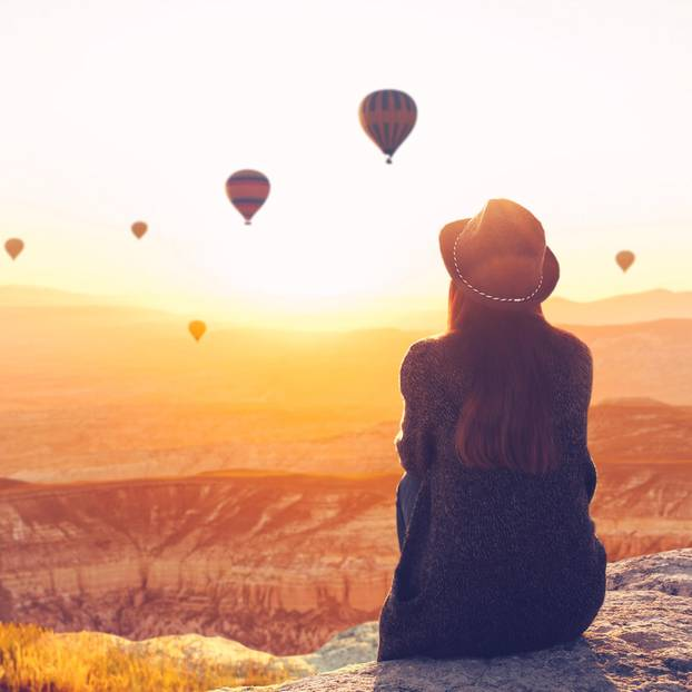 Horoskop: Eine Frau sitzt auf einem Hügel und beobachtet Heißluftballons