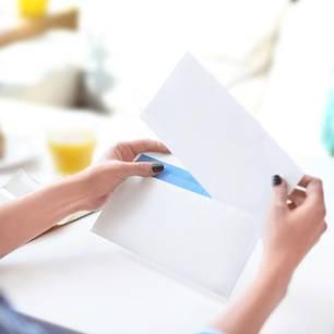 Briefumschlag richtig beschriften: Frau hält Brief in den Händen