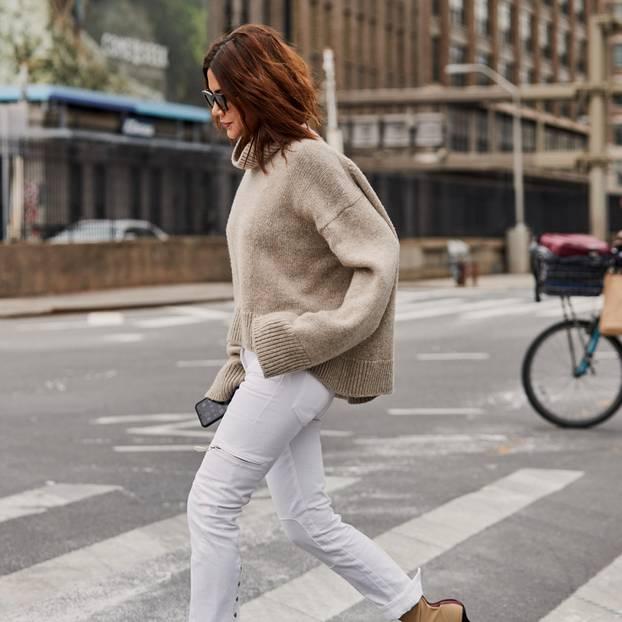 Pullover-Trends im Herbst: Frau mit Pullove rund weißer Hose