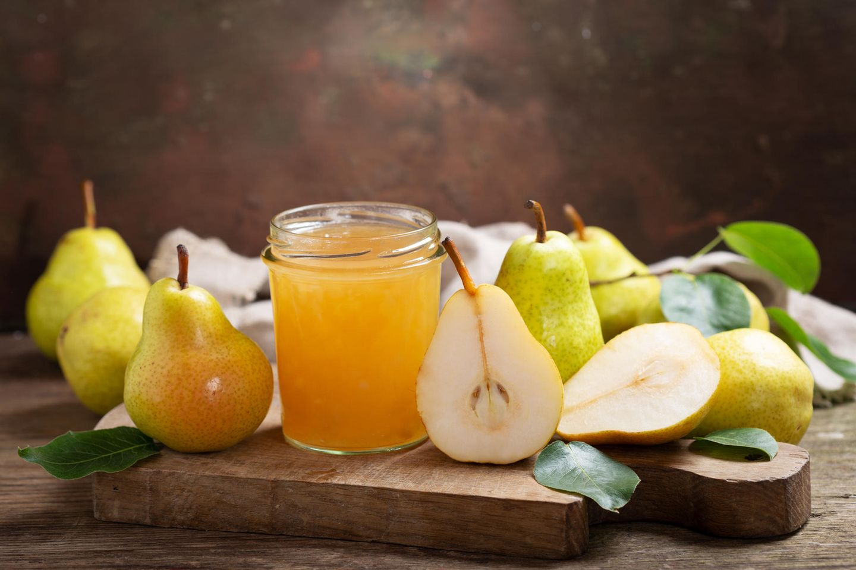 Birnengelee: Glas mit Birnengelee und Birnen auf einem Tisch