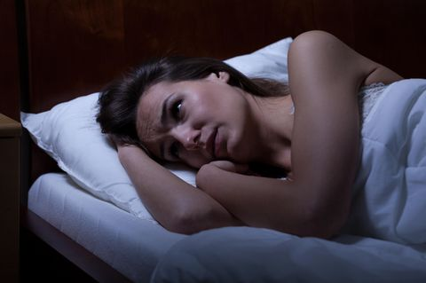Gründe für Schlafprobleme: Frau liegt wach im Bett