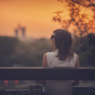 Horoskop: Eine Frau sitzt auf der Bank und die Sonne geht auf