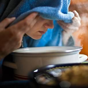 Inhalieren: Frau inhaliert über einer Schüssel