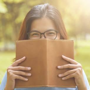 Buchhülle nähen : Frau hält sich offenes Buch vor das Gesicht