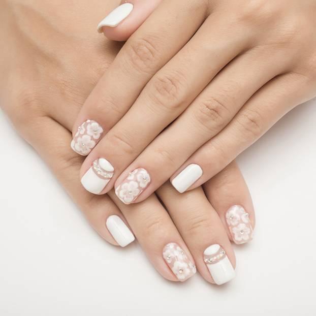 Hochzeitsnägel: Weiß lackierte Nägel mit Blumenmuster und Glitzersteinen