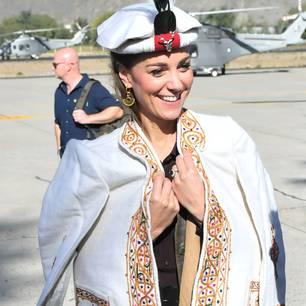 Unter ihrem bestickten Mantel trägt die Herzogin einen braunen Midirock, eine leichte Bluse, eine Lederweste und Wildlederstiefel.