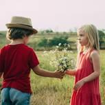 Erste Liebe: Ein Junge gibt einem Mädchen ein Strauß Blumen
