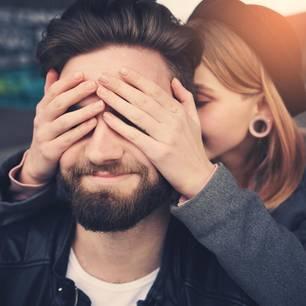 Reddit: Eine Frau hält einem Mann die Augen zu und flüstert ihm etwas ins Ohr