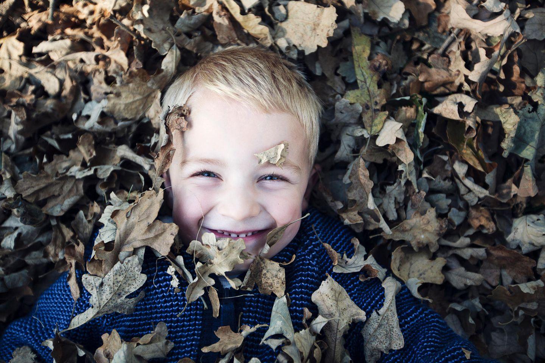 Oktober-Geburtstagskinder: Kleiner Junge im Laub