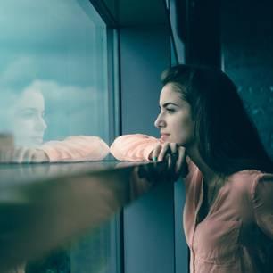 Selbstsabotage: So bekämpfst du deinen inneren Feind: Frau schaut nachdenklich aus dem Fenster