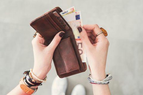 Dinge, für die wir zu viel Geld ausgeben: Hand mit Portmonnee