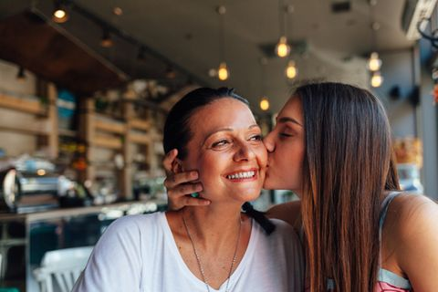Mutter-Tochter-Tattoo: Tochter küsst ihre Mutter auf die Wange