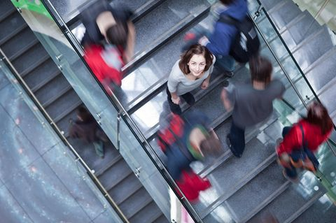 Krabbenkorb-Effekt: Eine Frau auf einer Rolltreppe umgeben von anderen