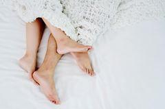 Phubbing: Ein Pärchen im Bett, man sieht nur die Füße