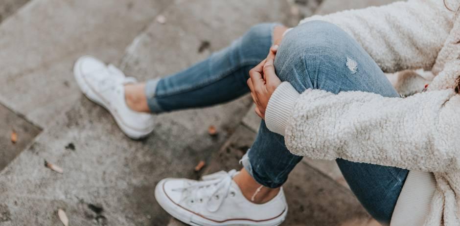 Igitt! Experten raten, unsere Jeans nicht zu waschen: Frau in Jeans auf Treppe sitzend
