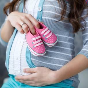 Fruchtbarkeit: Schwangere Frau hält Kinderschuhe