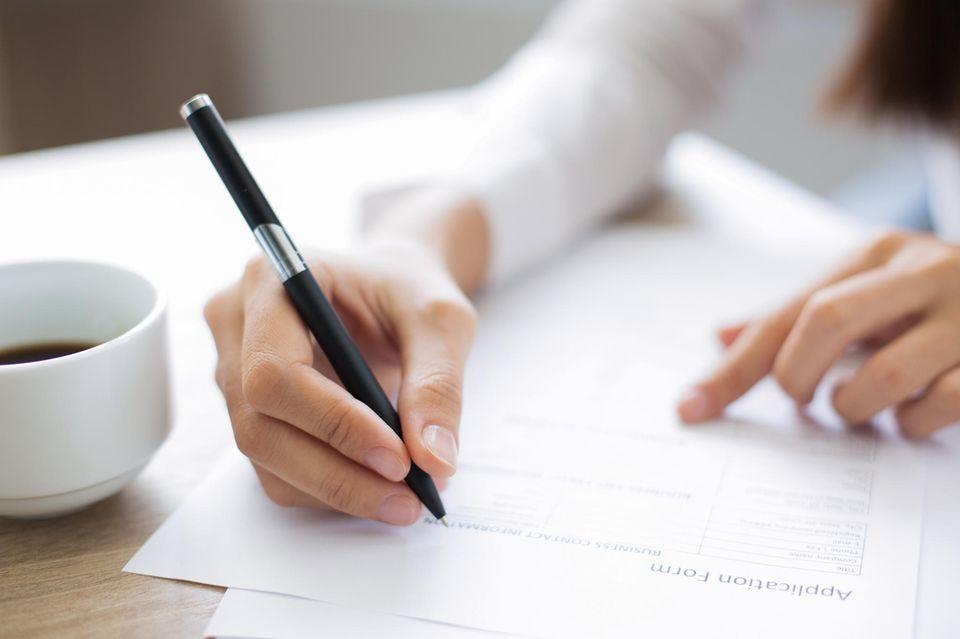 Lebenslauf unterschreiben: Frau schreibt auf Blatt