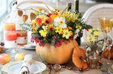 Tischdeko Herbst: Gedeckter Tisch in der Mitte ein Kürbis als Vase mit Blumen