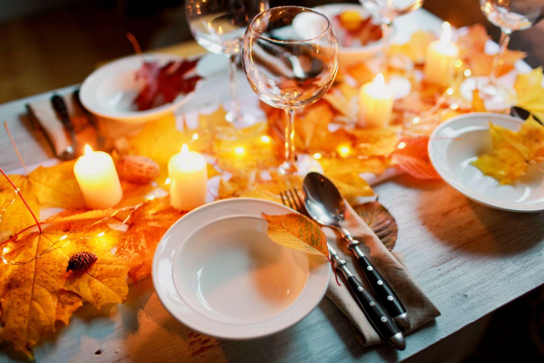 Tischdeko Herbst: Blätterdeko auf einem gedeckten Tisch