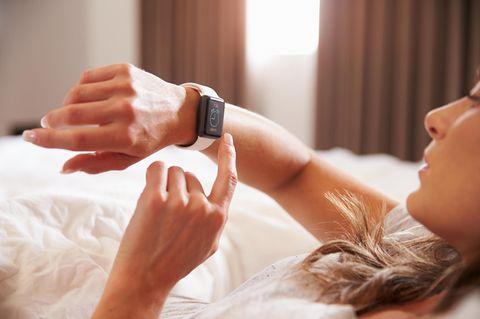 Uhrzeiten-Bedeutung: Eine Frau liegt im Bett schaut auf ihre Armbanduhr