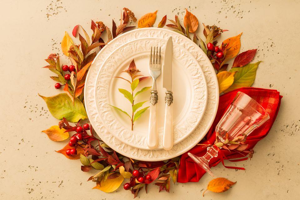 Tischdeko Herbst: Blätterdeko um einen Teller