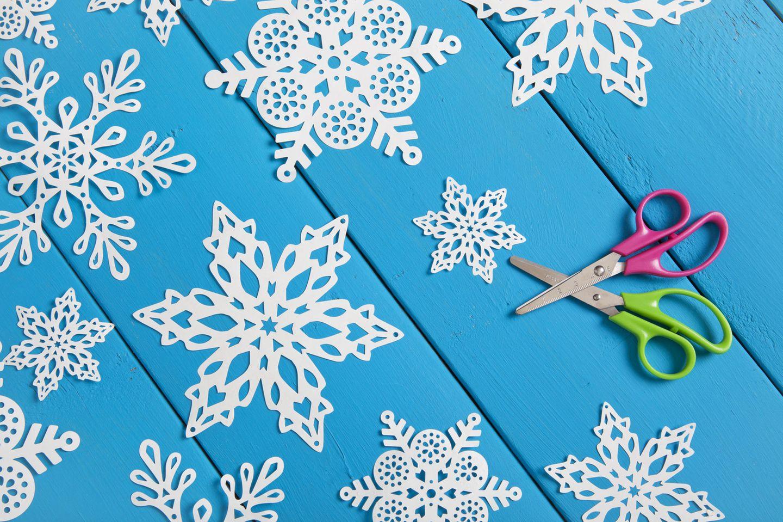 Bastelideen Winter: Papierschneeflocken auf blauem Untergrund