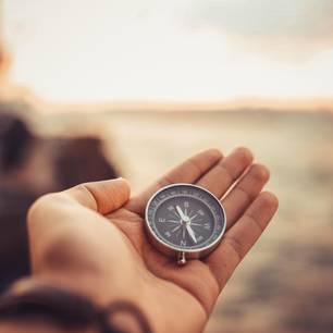 Horoskop: Eine Frau hält einen Kompass in der Hand