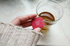 Lebensweisheiten: Eine Frau liest das Schild an einem Teebeutel