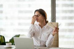 Schwächen im Vorstellungsgespräch: Frau fasst sich erschöpft ins Gesicht